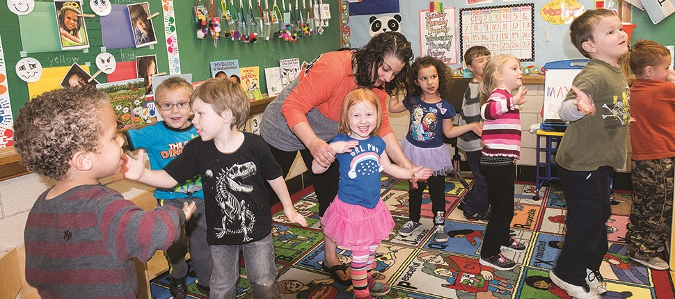 Preschool classroom with students and teacher dancing